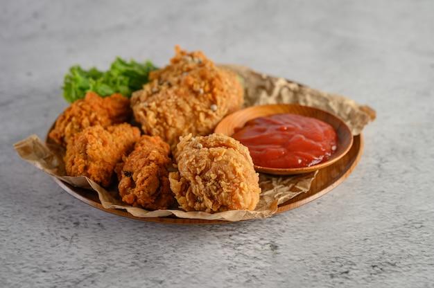 Knapperige gebraden kip op een plaat met tomatensaus