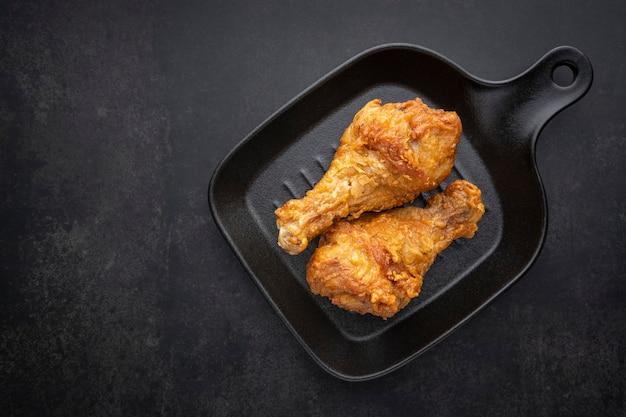 Knapperige gebraden kippentrommelstok met zwarte pan op de donkere toonachtergrond