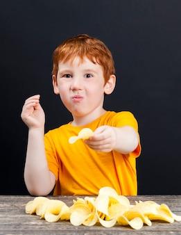 Knapperige heerlijke chips die een kleine jongen met rood haar eet, schadelijk voedsel