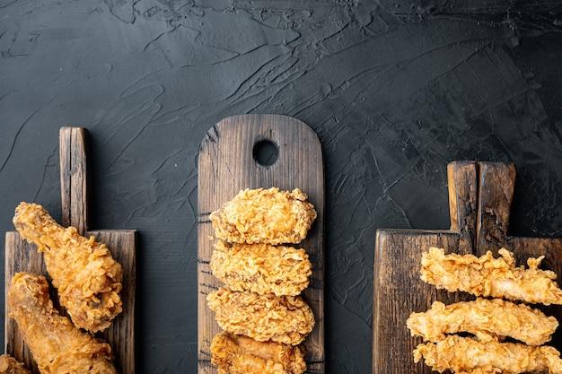 Knapperige kentucky fried chicken bezuinigingen op zwarte tafel, bovenaanzicht.