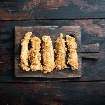 Knapperige kip sticks vlees op donkere houten tafel, bovenaanzicht.