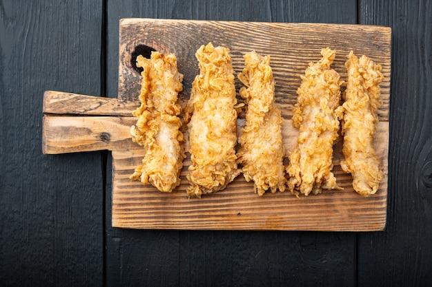 Knapperige kip sticks vlees op zwarte houten tafel, bovenaanzicht.