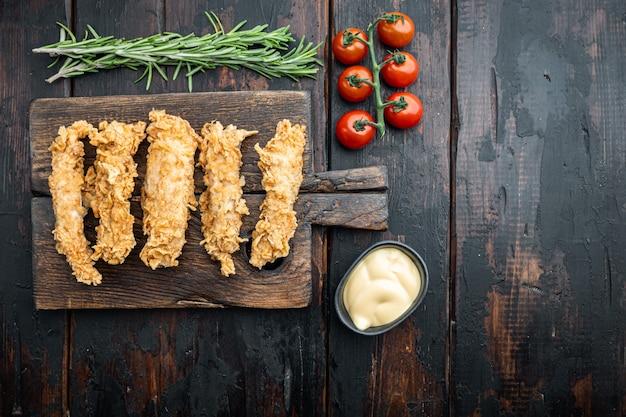 Knapperige kip stokken vlees op donkere houten tafel, plat leggen.