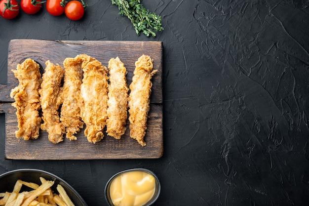 Knapperige kip stokken vlees op zwarte tafel, bovenaanzicht.