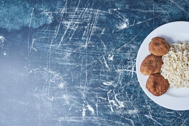 Knapperige kipnuggets en noedels.