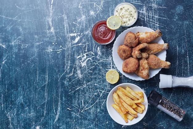 Knapperige kippenpoten met nuggets en aardappelen.