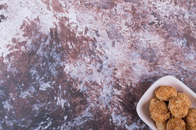 Knapperige koekjes in een wit keramiek schotel in de benedenhoek.
