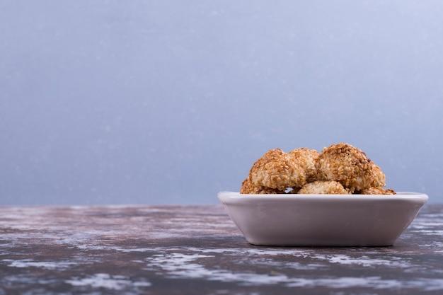 Knapperige koekjes in een witte ceramische schotel op blauw.