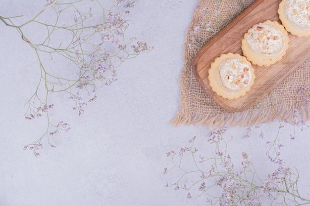 Knapperige koekjes op een houten bord op een stuk jute