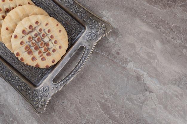 Knapperige koekjes op een sierlijk dienblad op marmer