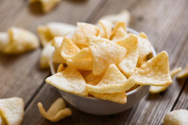 Knapperige kroepoek chips op witte kom en houten tafel achtergrond