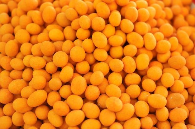 Knapperige met een laag bedekte pinda'sachtergrond. stapel gele eetbare ballen close-up. traditioneel oosters dessert.
