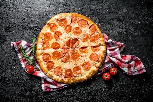 Knapperige pepperonispizza op een servet. op zwarte rustiek