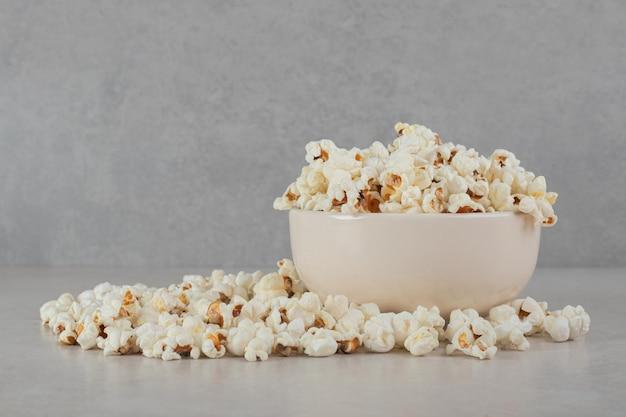 Knapperige popcorn in en rond een witte kom op marmeren oppervlak.