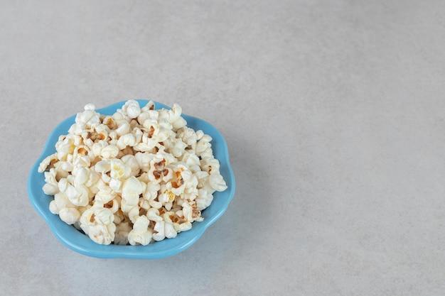 Knapperige popcorn op een kleine blauwe schotel op marmeren tafel.