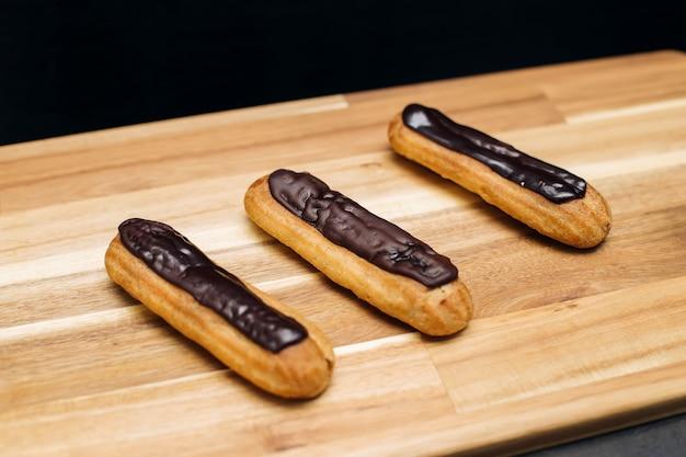 Knapperige romige cake met donkere chocolade is geplateerd op houten oppervlak
