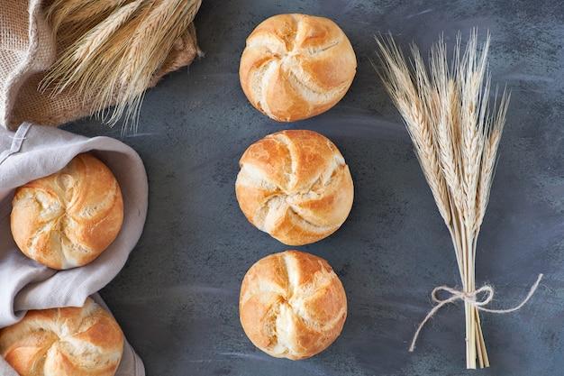 Knapperige ronde broodjes, bekend als kaiser- of wenen-broodjes met een bos tarweoren op donkergrijs