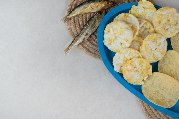 Knapperige snacks op blauw bord met droge vis