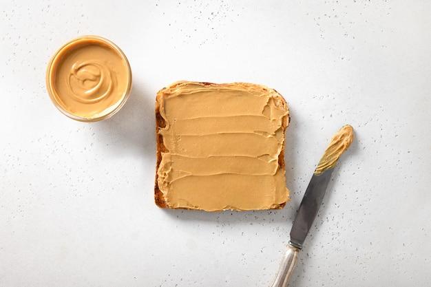 Knapperige toast met pindadeeg voor gezond ontbijt op wit.
