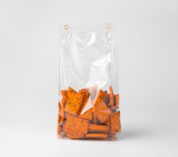 Knapperige tomatencrackers met knoflook en basilicum in een verpakkingszak op een licht bureau. zijaanzicht.