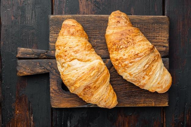 Knapperige verse croissants set, op oude donkere houten tafel achtergrond
