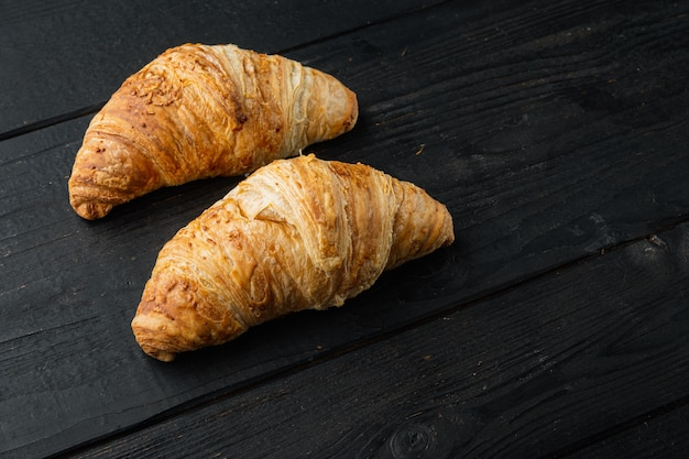 Knapperige verse croissants set, op zwarte houten tafel achtergrond