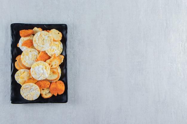 Knapperige volkoren rijstwafels en crackers op donkere plaat.