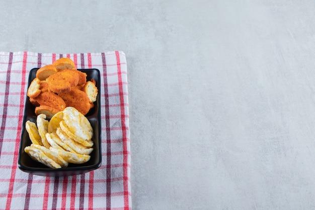 Knapperige volkoren rijstwafels en crackers op zwarte plaat.