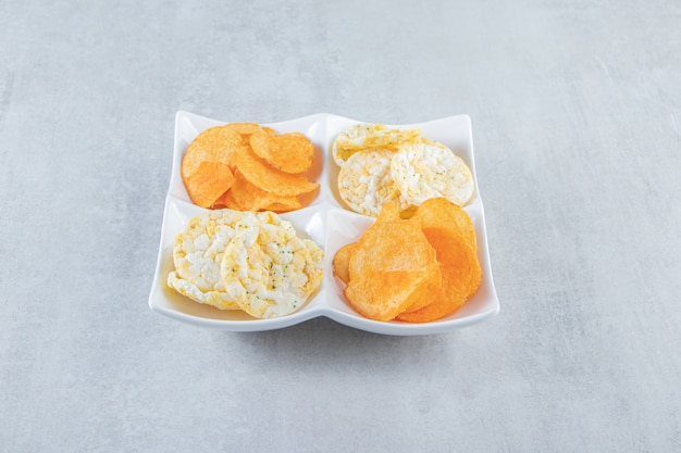 Knapperige volkoren rijstwafels en pittige chips in witte kommen.
