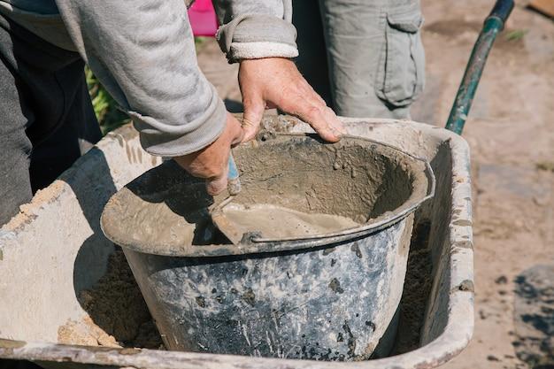 Kneden van cement voor het gieten van tuinpad, tuinbouwwerkzaamheden.