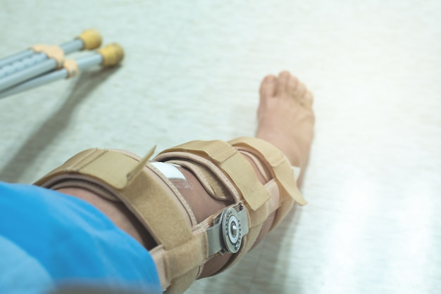 Knie met kniebrace ondersteuning na operatie met wandelstok van patiënt in ziekenhuis
