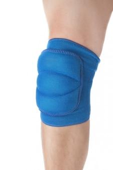 Kniebescherming bij wedstrijden op het mannelijke been. detailopname. op een witte muur.