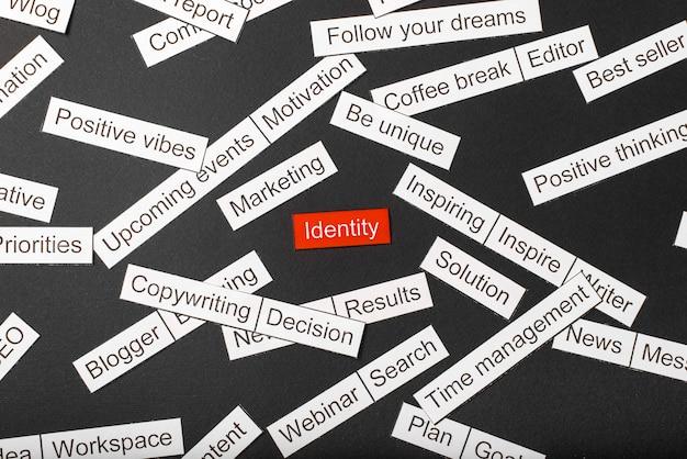 Knip papier inscriptie identiteit op een rode achtergrond, omringd door andere inscripties op een donkere achtergrond. word cloud concept.