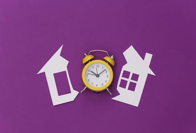 Knip papieren huis en wekker op een paarse achtergrond. scheiding.