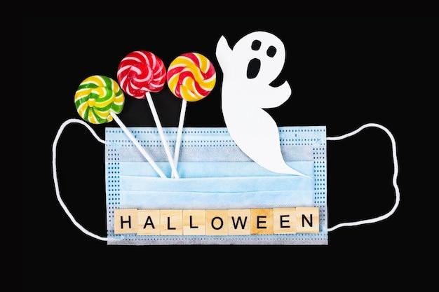 Knip papieren spook, kleurrijke lollies, medisch masker en woord halloween op zwart uit