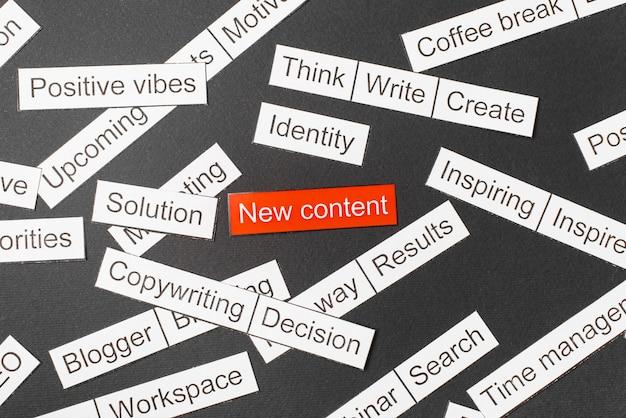 Knip papierinschrijving nieuwe inhoud op een rode achtergrond, omringd door andere inscripties op een donkere achtergrond. word cloud concept.