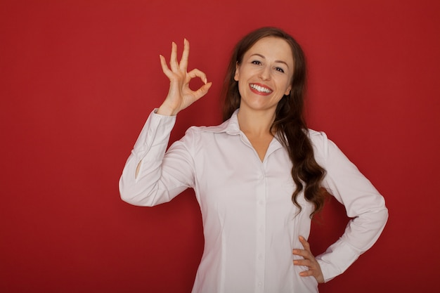 Knipogend mooi vrouwelijk model van de meisjes jong mooi leuk vrouw met donkerbruin haar in wit overhemd