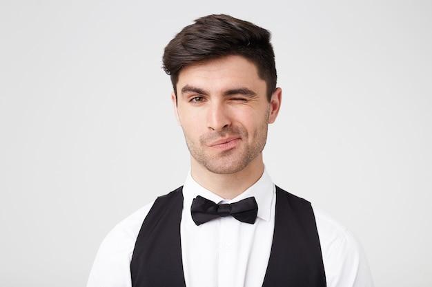 Knipogende knappe man, gekleed in zwart pak en vlinderdas, flirtend