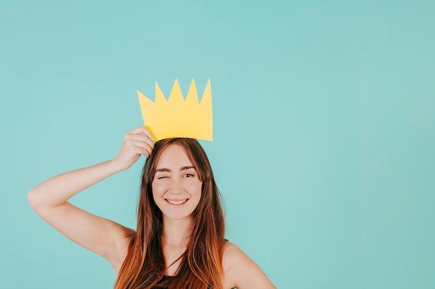 Knipogende vrouw met papieren kroon