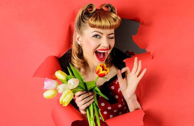 Knipogende vrouw met tulpen toont teken ok. glimlachend meisje dat met boeket van bloemen door document kijkt.
