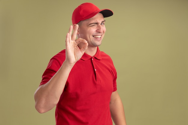Knipperde glimlachende jonge bezorger met uniform en pet met goed gebaar geïsoleerd op olijfgroene muur met kopieerruimte