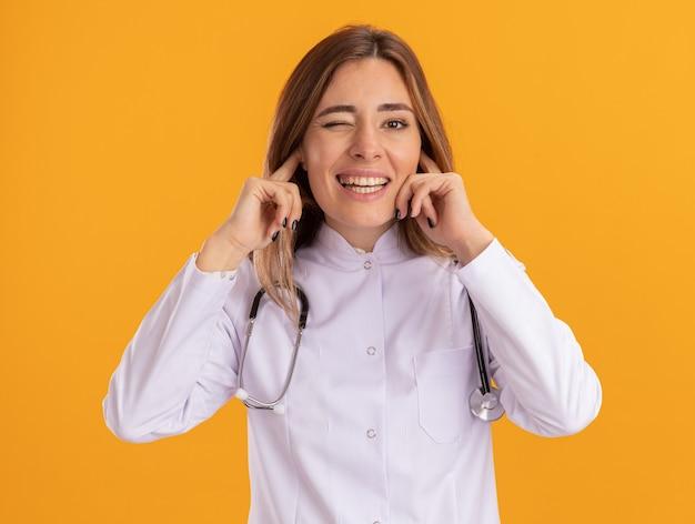 Knipperde jonge vrouwelijke arts die medische mantel draagt met stethoscoop gesloten oren geïsoleerd op gele muur