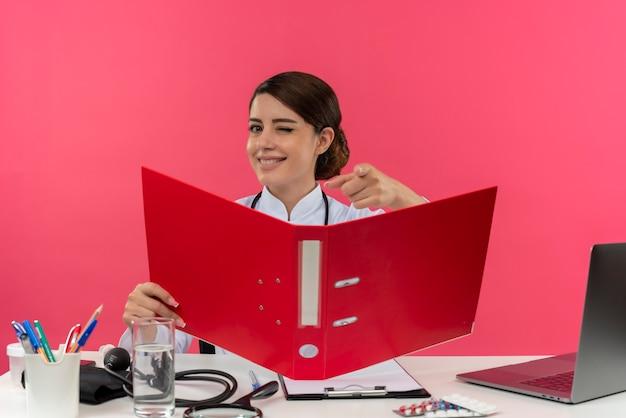 Knipperde lachende jonge vrouwelijke arts medische mantel dragen met stethoscoop zittend aan bureau werken op computer met medische hulpmiddelen houden map toont u gebaar op roze muur met kopie ruimte