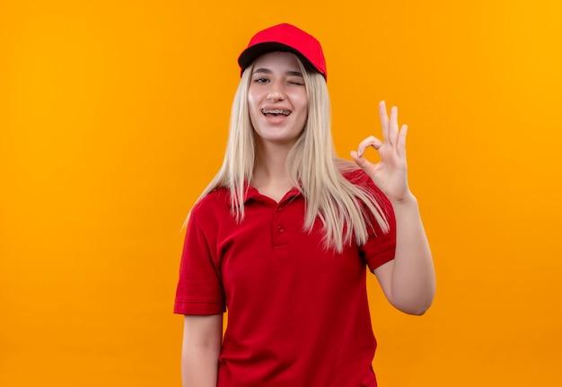Knipperde levering jonge vrouw, gekleed in rode t-shirt en pet in tandsteun met ok gebaar op geïsoleerde oranje muur
