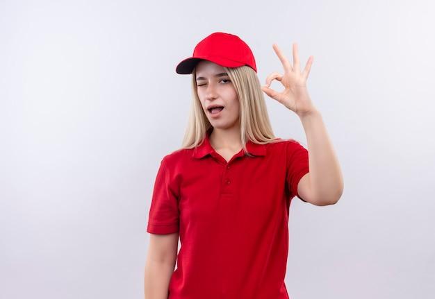 Knipperde levering jonge vrouw, gekleed in rode t-shirt en pet met ok gebaar op geïsoleerde witte muur