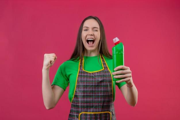 Knipperde vrolijke schoonmakende jonge vrouw die eenvormig holdingsreinigingsmiddel draagt dat ja gebaar op geïsoleerde roze muur toont