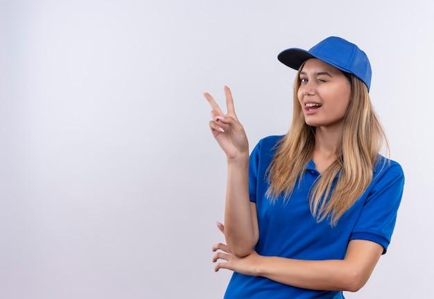 Knipperend jong leveringsmeisje die blauw uniform en pet dragen die vredesgebaar tonen dat op witte muur met exemplaarruimte wordt geïsoleerd