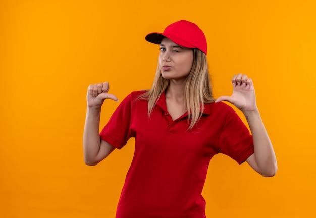 Knipperend jong leveringsmeisje die rood uniform dragen en glb-punten zelf geïsoleerd op oranje achtergrond
