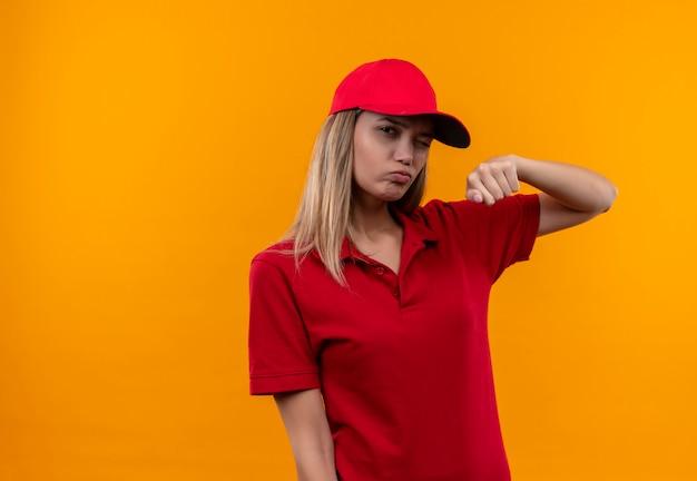 Knipperend jong leveringsmeisje die rood uniform en glb dragen die vuist opheffen die op oranje achtergrond wordt geïsoleerd