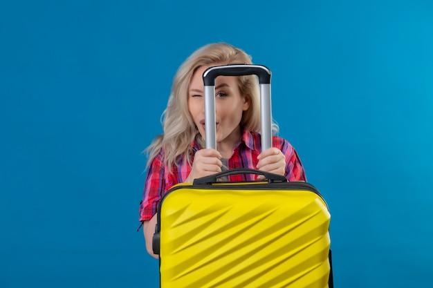 Knipperende jonge vrouwelijke reiziger die de rode koffer van de overhemdsholding op geïsoleerde blauwe muur draagt